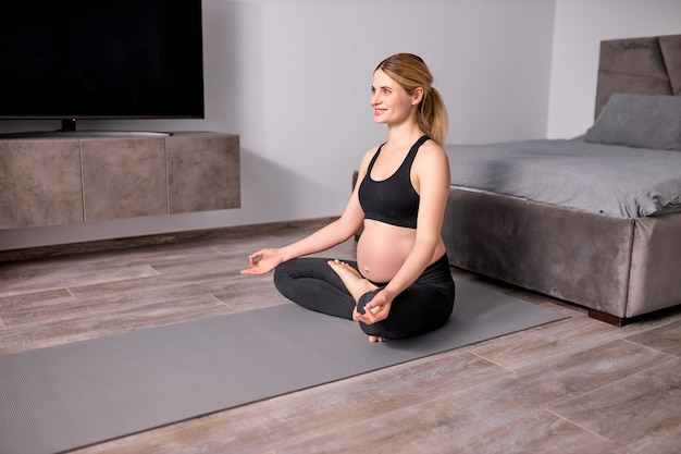 Pleasant pregnant woman meditating on floor at home with crossed legs