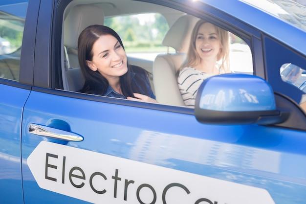 즐거운 승차감. 창 밖을보고 그녀의 친구와 함께 차에 앉아있는 동안 웃고 행복 좋은 매력적인 여자