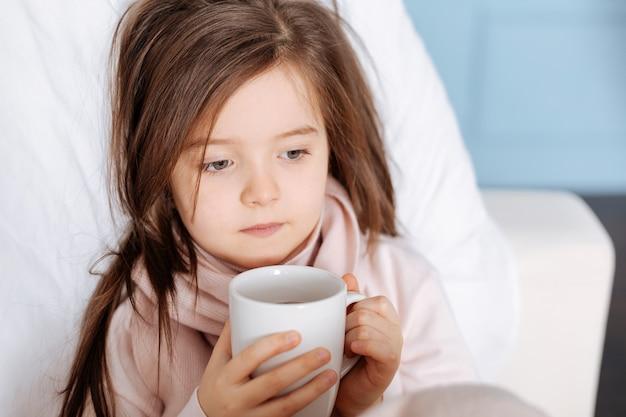 Приятная больная маленькая девочка пьет чай и чувствует себя плохо, лежа в постели