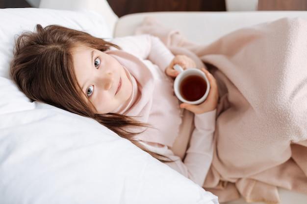 Приятная больная маленькая девочка смотрит на вас и пьет чай, чувствуя усталость