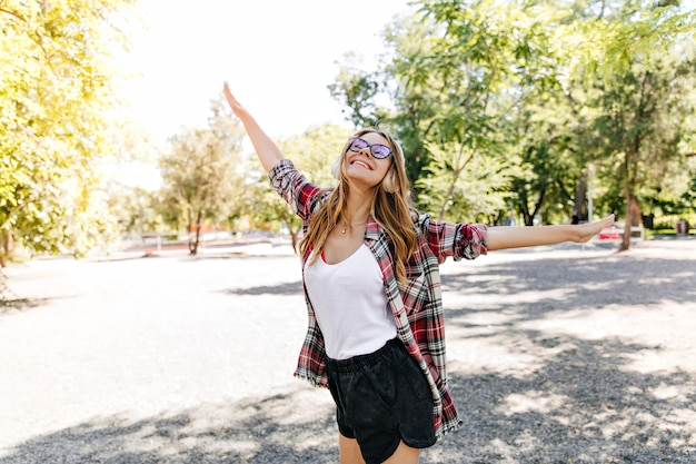 여름 공원에서 춤추는 즐거운 슬림 소녀. 긍정적 인 백인 여자 재미 자연에 포즈.