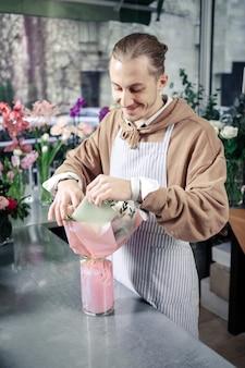 心地よい笑顔。花を見ながら頭を下げて喜んでポジティブな男性