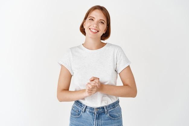 Piacevole ragazza sorridente che sembra amichevole, tenendosi per mano, consulente pronto ad aiutare, in piedi sul muro bianco