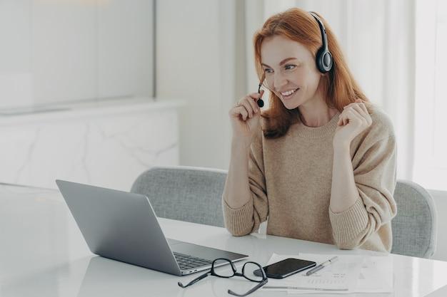 Приятная улыбающаяся рыжая женщина в гарнитуре общается с коллегами во время видеозвонка на ноутбуке