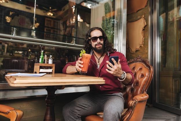 카페에서 휴식을 취하는 동안 스마트 폰을 사용하는 즐거운 세련된 남자