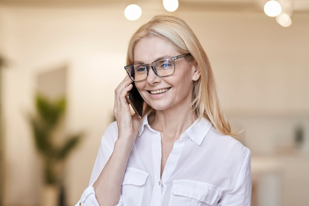 Pleasant talk attractive mature woman with blonde hair and glasses in casual wear talking on her