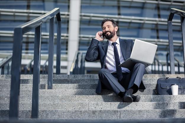 歓談。電話で話し、ラップトップを使用して陽気な笑顔のビジネスマン