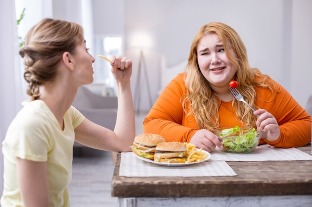 Pleasant talk. dissatisfied fat woman eating a salad and talking with her slim friend eating fast food
