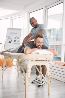 Приятная терапия. веселый позитивный человек, лежа на медицинской кушетке, наслаждаясь массажем