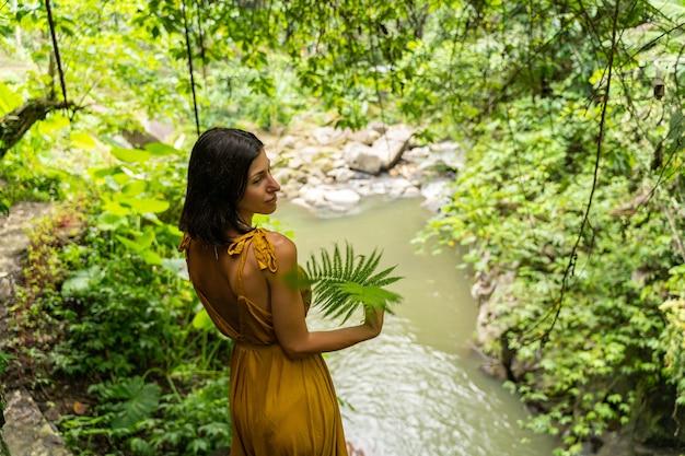 楽しい考え。シダの葉でカメラにポーズをとっている間彼女の頭を回すかわいい若い女性
