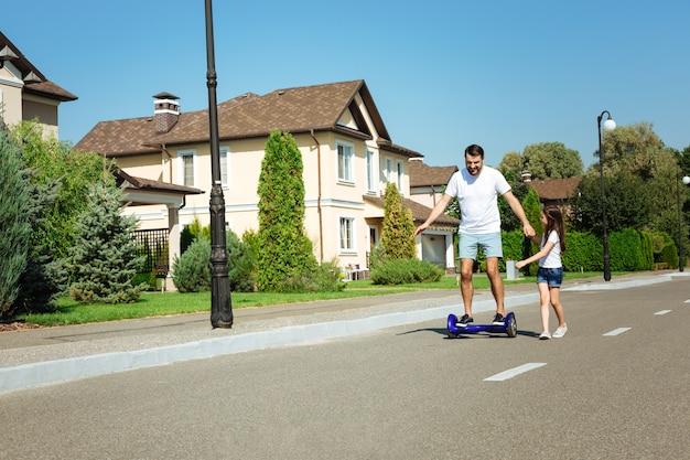 함께 즐거운 시간. 그의 작은 딸이 그를 따르고 그의 손을 잡고있는 동안 거리를 호버 보드를 타고 쾌활한 젊은 아버지