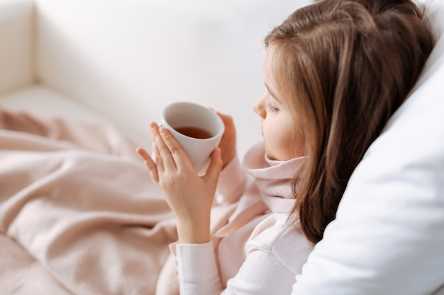 Приятная уставшая маленькая девочка пьет чай и отдыхает дома при плохом самочувствии