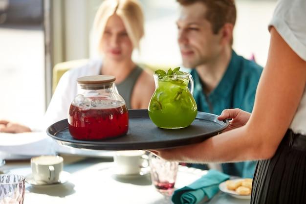 Приятный официант подает клиентам напитки на подносе