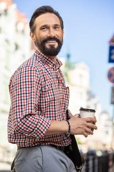 Приятной прогулки. веселый взрослый мужчина улыбается во время работы по улице
