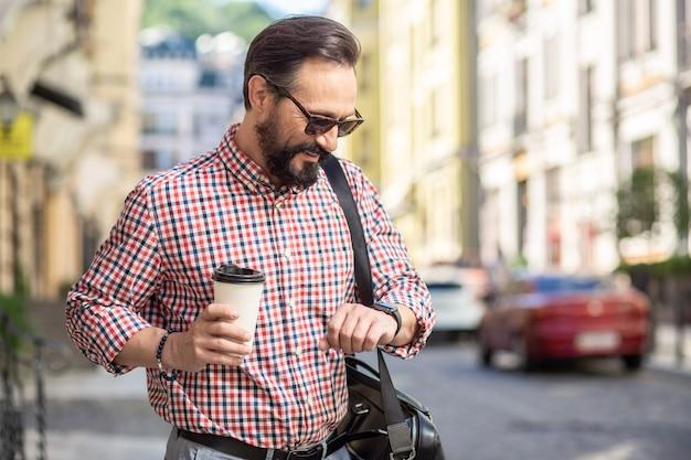 Приятной прогулки. талия позитивного мужчины смотрит на часы, попивая кофе на улице