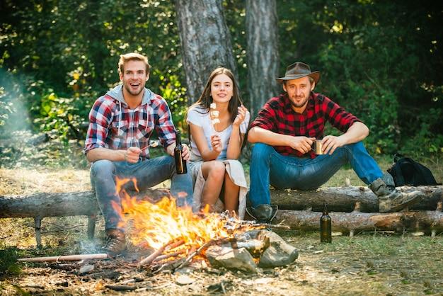 自然の会社の友達のピクニックやバで焚き火を楽しんでいるキャンプファイヤーの幸せな友達の近くの楽しい週末...