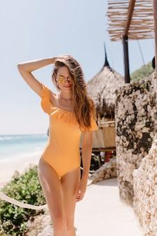 피서지에서 포즈를 취하는 동안 그녀의 머리를 만지고 즐거운 백인 여성 모델. 오렌지 수영복과 그녀의 방갈로 주위를 산책하는 선글라스에 슬림 그을린 여자의 야외 촬영.