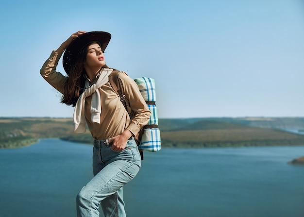 Pleasant woman enjoying sunny weather at the lake