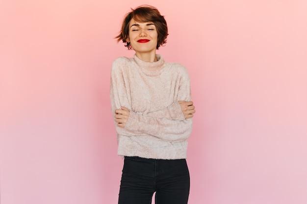 目を閉じてポーズをとるセーターの楽しい女性