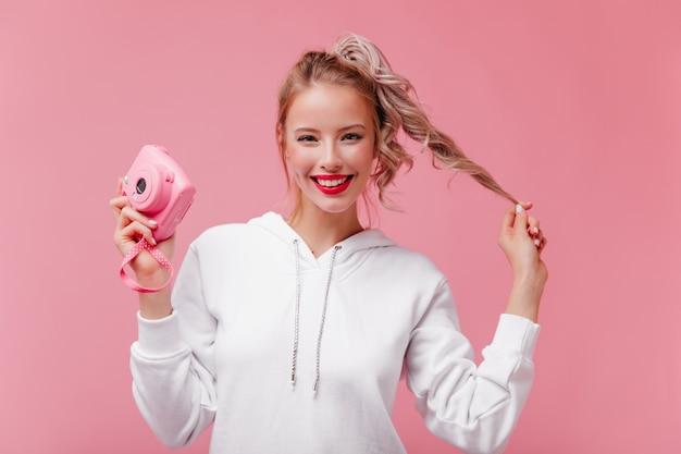 ピンクの壁で笑っている楽しい女性