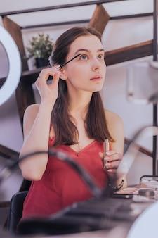 楽しい女性。彼女の顔を構成するスタイリッシュな赤いブラウスを着て楽しい魅力的な女性