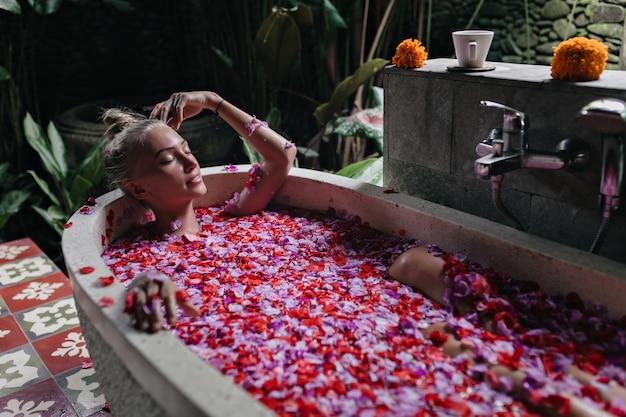 目を閉じて風呂に横たわっている日焼けした肌の気持ちの良い女性。バラの花びらでスパを楽しんでいるかわいい金髪の女性の屋内ショット。
