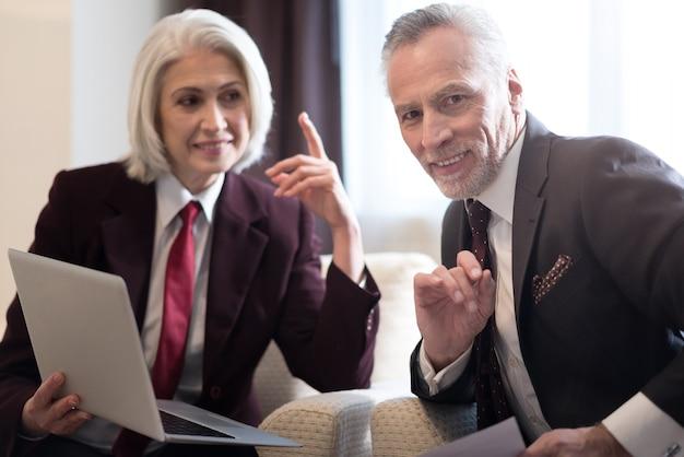 快適な労働時間。彼女の同僚を見て、ラップトップを持ってオフィスに座っている陽気な笑顔の高齢の実業家