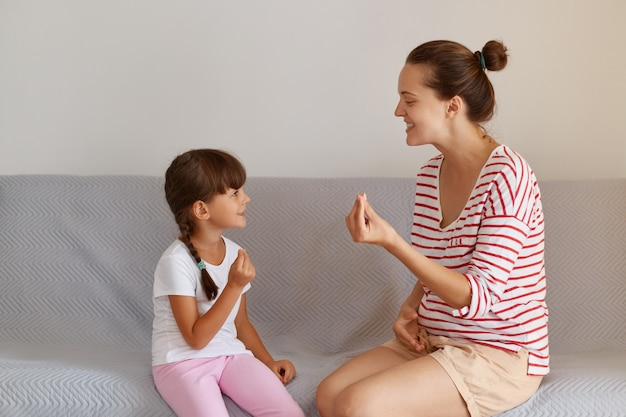 어린 여성 아이에게 올바른 발음을 가르치는 유쾌한 젊은 성인 언어 치료사, 실내에서 어린 소녀와 함께 언어 결함 또는 어려움에 대해 일하는 전문 물리 치료사.