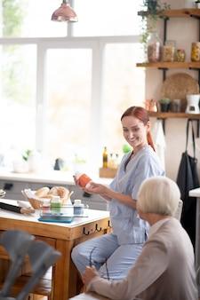 Pleasant young caregiver preparing medication for pensioner