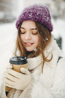 Приятная девушка с закрытыми глазами в теплой одежде держит в руках горячий кофе с собой, позируя на открытом воздухе.