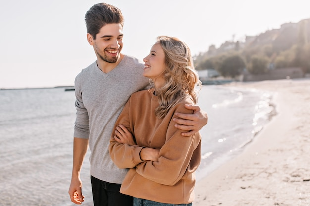 Pleasant young man embracing girlfriend on nature. outdoor portrait of pleased blonde girl posing at sea with husband.