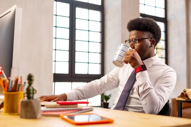 オフィスに座ってお茶を一口飲む楽しい青年
