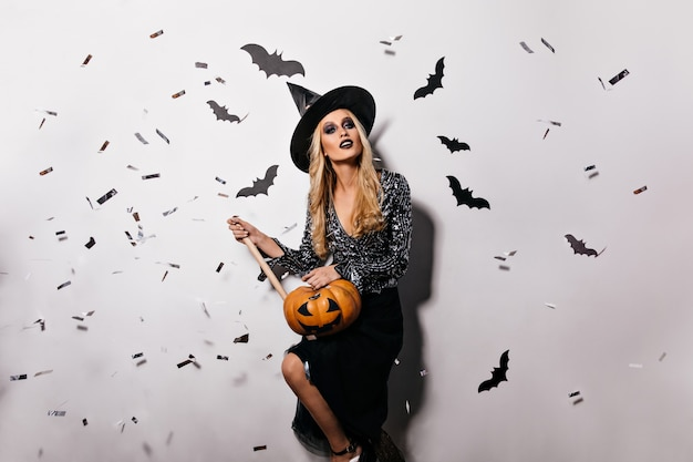 벽에 박쥐와 함께 포즈를 취하는 즐거운 젊은 마녀. 할로윈 호박을 들고 예쁜 금발 뱀파이어 소녀입니다.