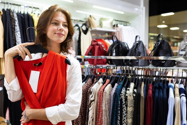 Pleasant young woman buys red dress for evening date at luxury boutique