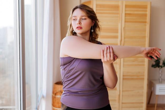 Приятная молодая женщина, держащая ее за руку, делая растяжку после тренировки