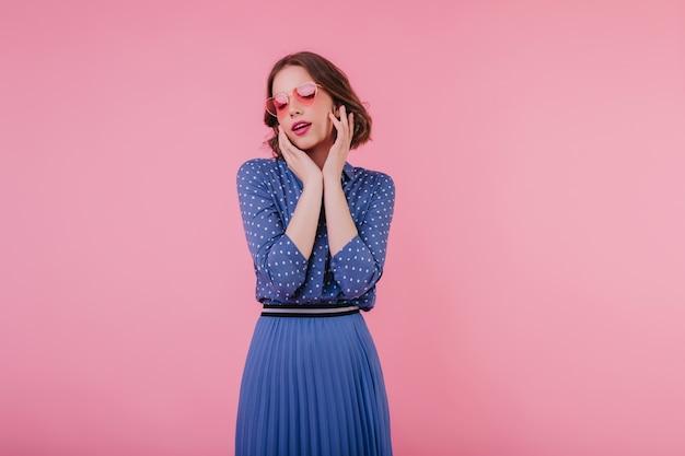 目を閉じてポーズをとる長い青いスカートの楽しい若い女性。ピンクの壁に立っているサングラスのjocund巻き毛の女性モデル。