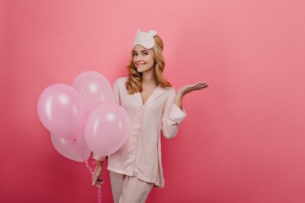 그녀의 생일 파티를 기다리는 실크 잠옷에 즐거운 젊은 여자. 밝은 벽에 미소로 포즈를 취하는 금발 물결 모양의 머리를 가진 우아한 소녀.