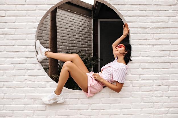 レンガの壁にポーズをとる楽しい若い女性。入れ墨のヨーロッパの女性の屋外ショット。