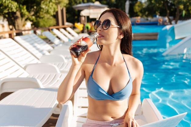 Приятная молодая женщина, сидящая у бассейна