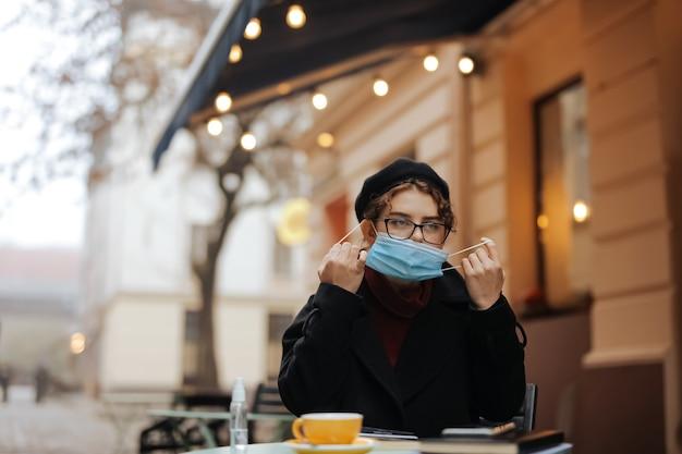 열린 된 카페 테라스에 앉아있는 동안 의료 마스크를 벗고 즐거운 젊은 여자. 야외에서 신선한 뜨거운 커피를 즐기는 매력적인 아가씨.