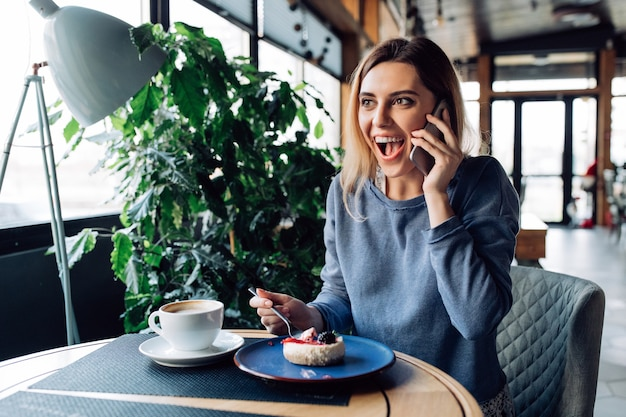 Pleasantly surprised girl having phone conversation, eating dessert and drinking coffee