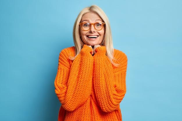Piacevolmente sorpreso felice bionda donna adulta tiene le mani sotto il mento sorride ampiamente scioccato per ricevere un presente inaspettato vestito con un maglione lavorato a maglia sciolto