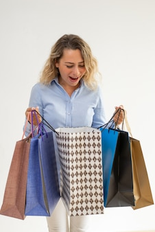 Pleasantly surprised lady opening shopping bag