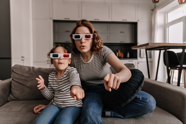 Pleasantly surprised mother and daughter are sitting on sofa in 3d glasses and watching movie.