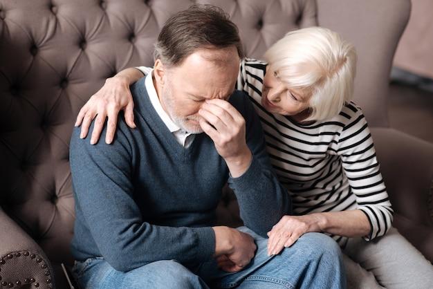 Пожалуйста, успокойся. пожилая женщина сидит и обнимает мужа в депрессии дома.