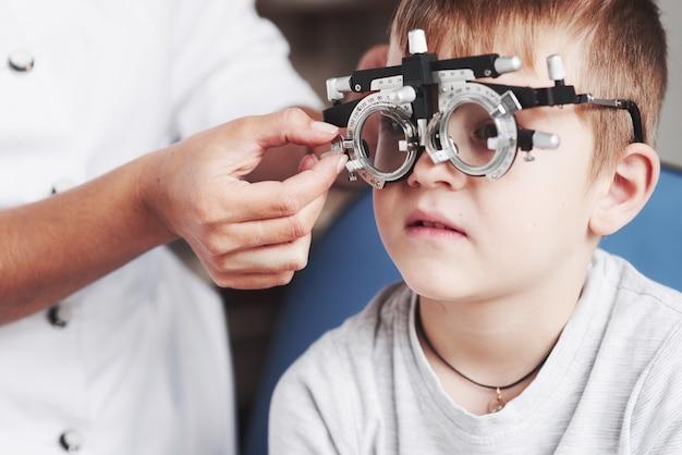集中してください。医院に座って視力をテストした子供。