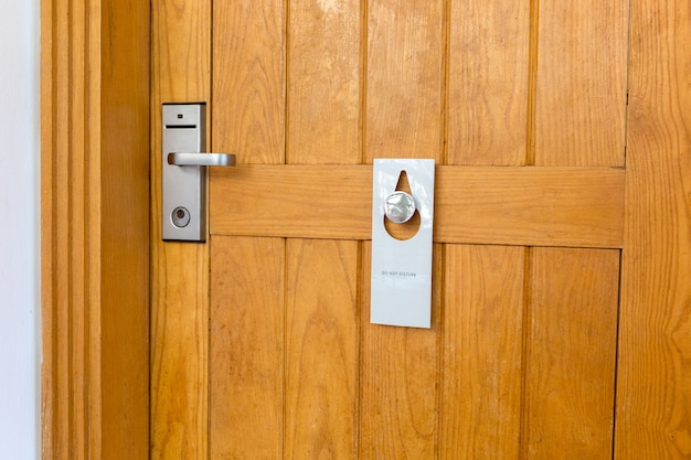 Please do not disturb sign on closed wooden door of hotel room