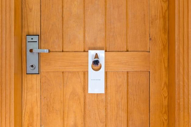 Please do not disturb sign on closed wooden door of hotel room