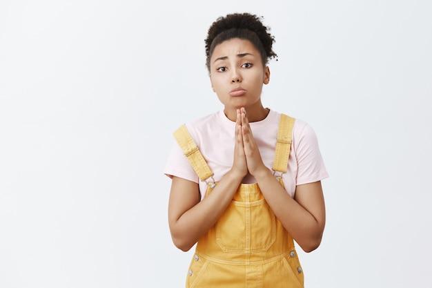 前回、約束してください。黄色の流行のオーバーオールを着た幼稚な浅黒い肌の少女。手をつないで祈り、助けを求めながら唇をふくれっ面とすぼめている