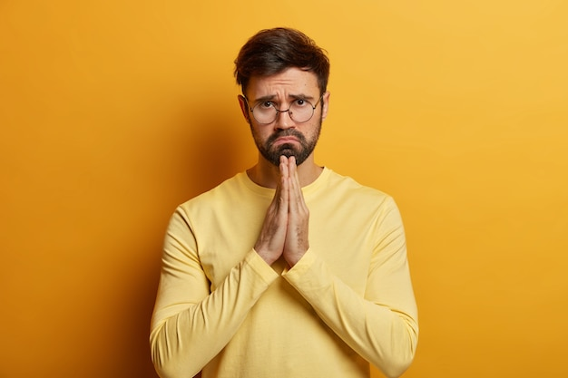 Please, forgive me. depressed unshaven man presses palms and makes apologize, has innocent gaze, begs for help, wears spectacles, yellow jumper, looks with pity face. male prayer asks to do favor